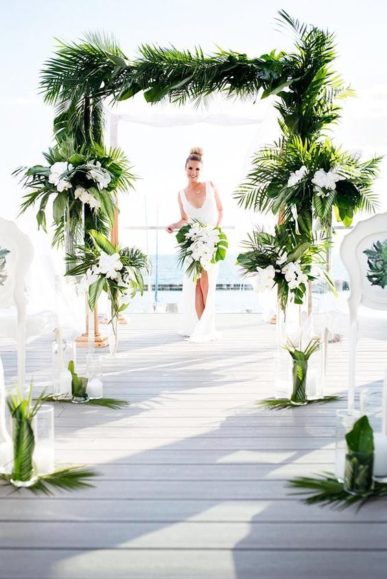 a chic wedding arch fully covered with tropical leaves and white orchids and matching arrangements to line up the aisle