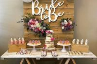 a cool dessert table with a wooden backdrop with greenery, blooms and white balloons and lots of desserts