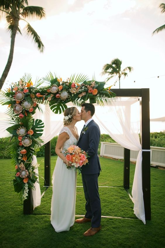 a cool tropical wedding arch in dark wood, with airy fabric, tropical leaves and bright blooms and king proteas