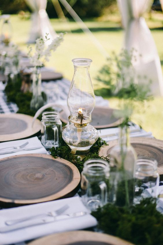 a cozy rustic or woodland tablescape with wood slices, moss, lanterns and jar mugs
