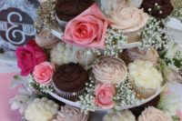 a cupcake stand with sweets and pink blooms and baby's breath is an amazing and cool idea for a party