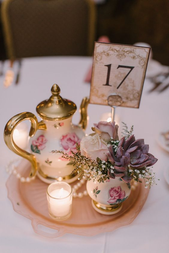 a cute vintage inspired centerpiece with some flower printed porcelain, succulents and a candle