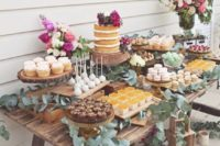a dessert table decorated with eucalyptus features lots of desserts and sweets plus a cake