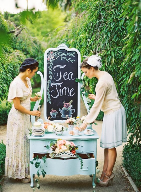 a dessert table of a vintage sideboard, lots of desserts, tea cups and a chalkboard backdrop
