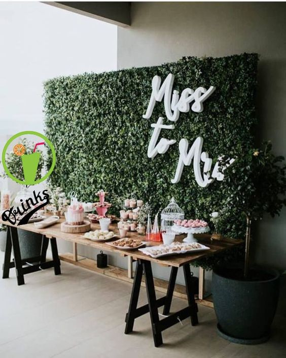 a dessert table with lots of sweets and a chic living wall backdrop with typography