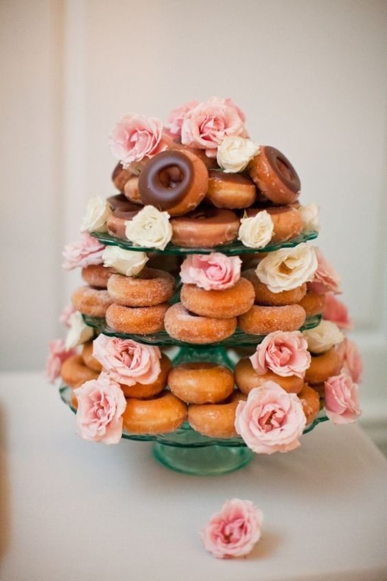 a donut tower with usual and glazed donuts and pink and neutral blooms for a bridal shower