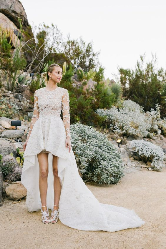 a dreamy lace applique high low wedding dress with a bodice with long sleeves and a high neckline plus a high low skirt with a long train and lace shoes