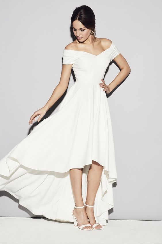 a dreamy off the shoulder plain high low wedding dress with a pleated skirt, white ankle strap shoes for a modern and romantic look