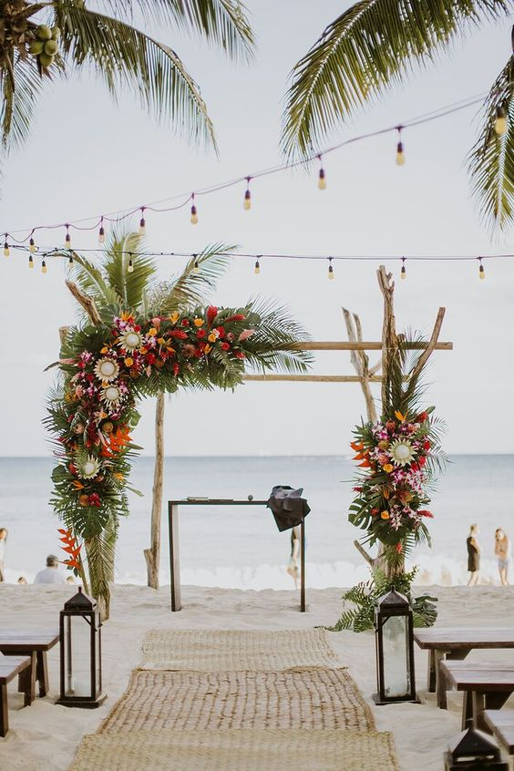 a driftwood tropical wedding arch decorated with greenery, with red, yellow, blush and orange blooms