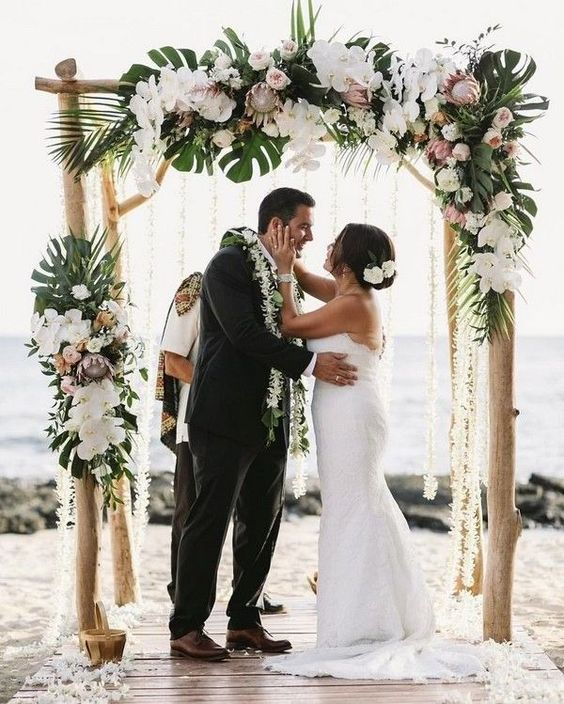 a driftwood wedding arch decorated with monstera leaves, white orchids and blush king proteas and peonies