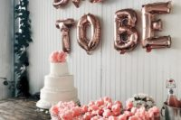 a drink station with pink champagne and cotton candy plus a wedding cake and cool letters on the backdrop