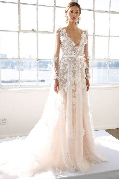 a feminine floral lace applique wedding dress with long sleeves and a plunging neckline