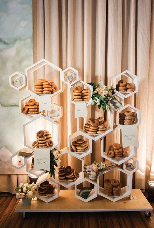 a fun hexagon wedding dessert stand with greenery and blooms can be used not only for donuts but for many other sweets, too