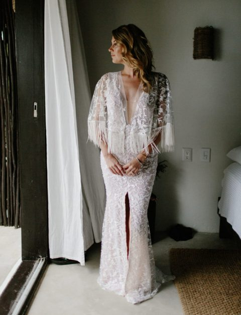 a glam boho gown with lace appliques, a plunging neckline, a front slit and long fringe on the bell sleeves