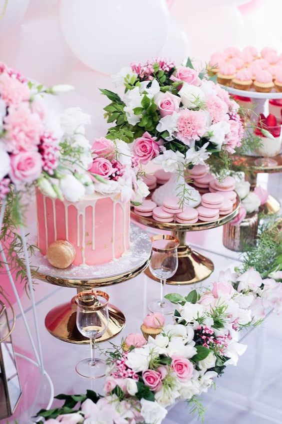 a gorgeous pink tea party table with macarons, a cake and lush white and pink floral decorations