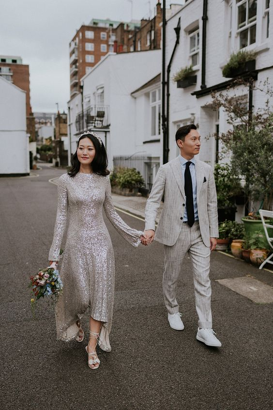 a gorgeous silver sequin high low A-line wedding dress with a high neckline, bell sleeves, lace up shoes and a crown for a glam look