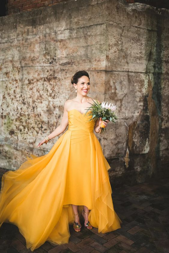 a gorgeous yellow A-line modern wedding dress with a wrapped bodice and a high low skirt with a train for a wow effect