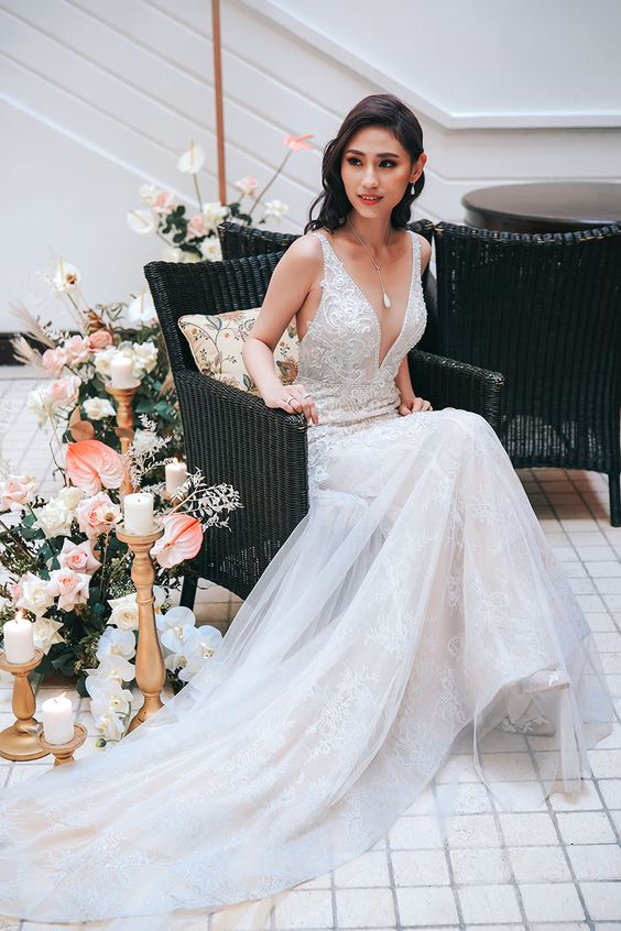 a gorgeous lace sheath wedding dress with thick straps, a plunging neckline and a train