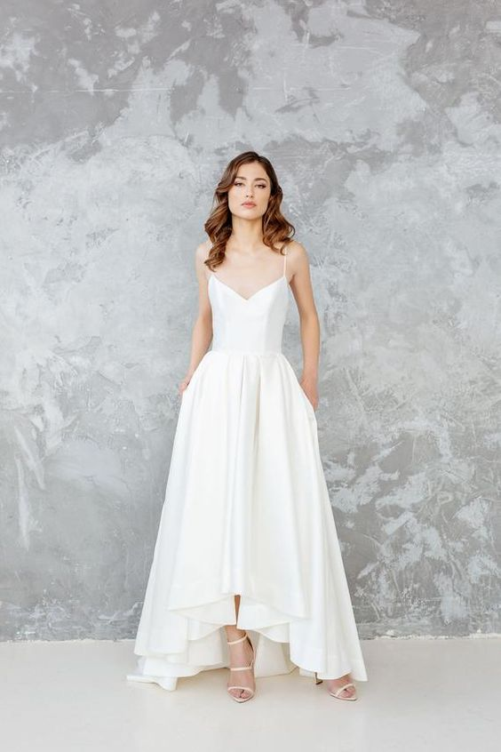 a lovely minimalist A-line wedding dress with a V-neckline, spaghetti straps, a pleated skirt with pockets and minimalist strap heels