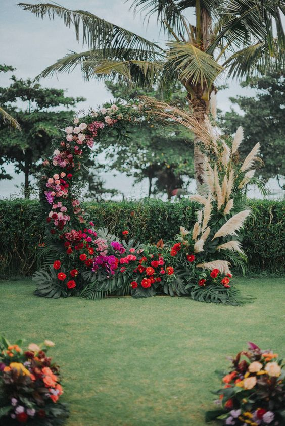 a lush round wedding arch with pampas grass, pink, blush, red and fuchsia blooms and tropical leaves