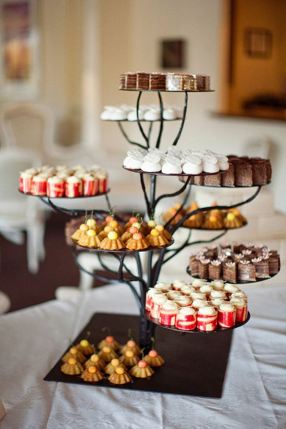 a metal tree-like wedding dessert stand is a very creative idea for a woodland or some relaxed rustic wedding