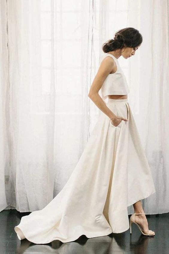 a minimalist two-piece wedding dress with a sleeveless crop top and a pleated skirt with a short train and pockets