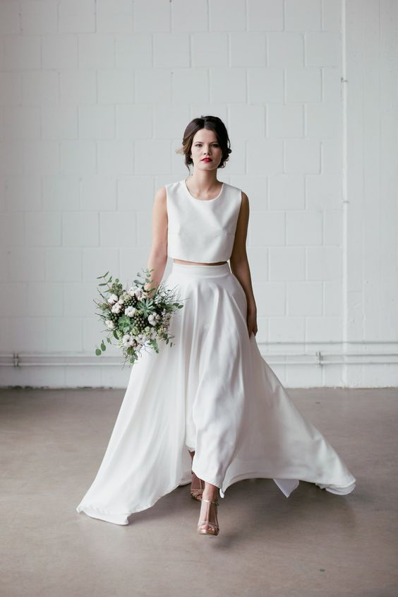 a minimalist two-piece wedding dress with a sleeveless crop top with a scoop neckline, a pleated plain high low skirt with a train