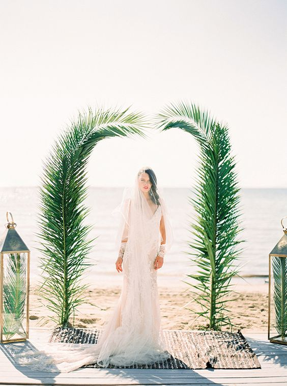 a minimalist wedding arch decorated with palm leaves is all you need to frame you two on the beach