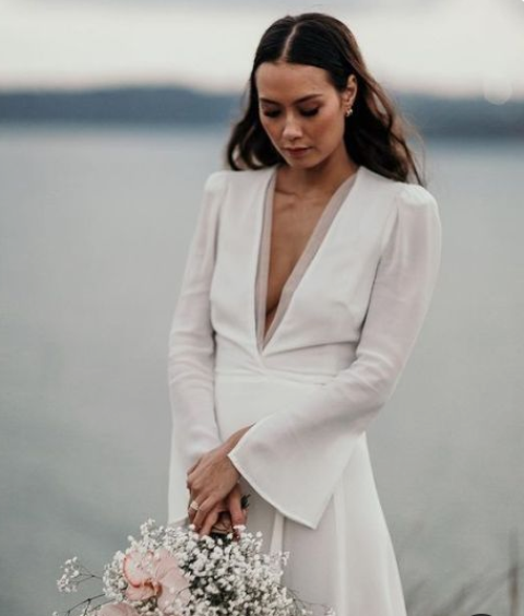 a minimalist wedding dress with a plunging neckline and bell sleeves for a touch of boho