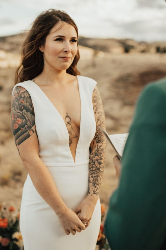 a modenr plain sheath wedding dress with a plunging neckline, no sleeves showing off the tattoos