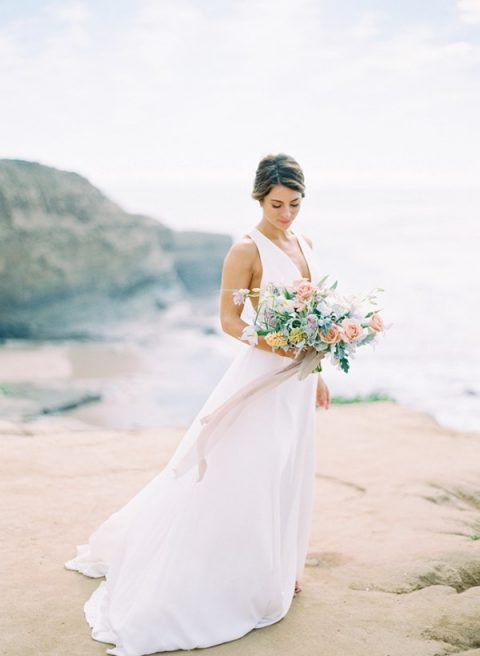 a modern A-line wedding dress with thick straps, a plunging neckline and a train