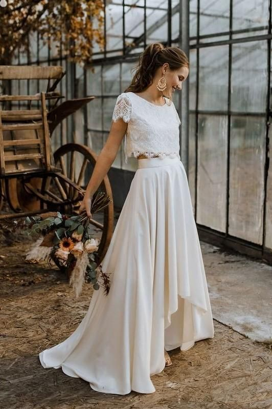 a modern and casual wedding separate with a lace crop top with short sleeves and a high neckline, a pleated skirt with a train