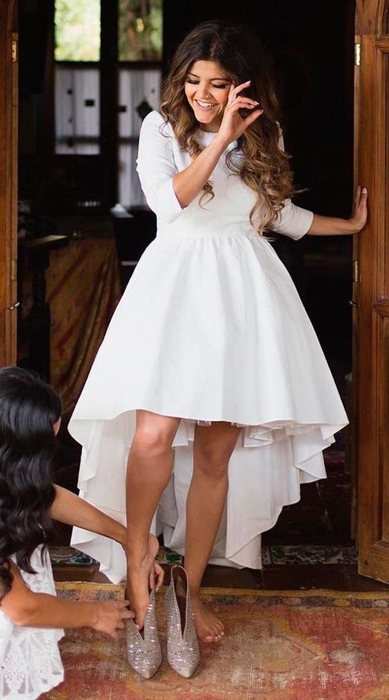 a modern and chic plain high low wedding dress with short sleeves and a high neckline plus shiny booties for a glam look