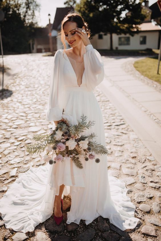 a modern and lovely A-line wedding dress with puff sleeves, a plunging neckline, a high low skirt with a train and burgundy shoes