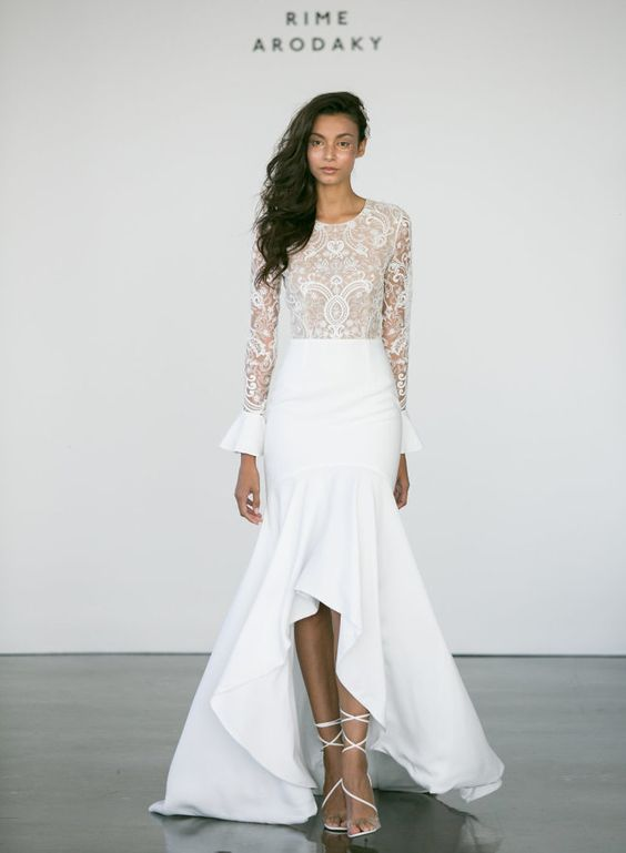 a modern mermaid wedding dress with a lace bodice with long bell sleeves, a high neckline, a plain mermaid ruffle high low skirt and lace up shoes
