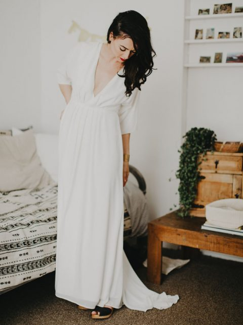 a modern plain wedding gown with a plunging neckline, long sleeves plus black mules
