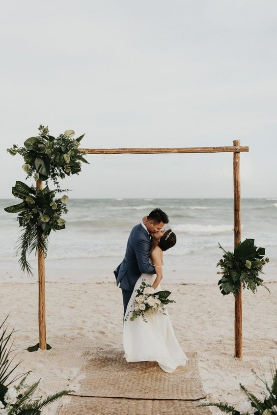 a modern tropical wedding arch decorated with greenery and tropical leaves is stylish and simple