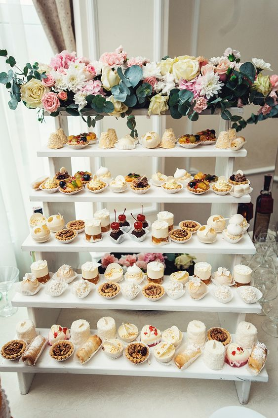 a modern white ladder dessert stand decorated with neutral, pink blooms and greenery is ideal for any modern wedding