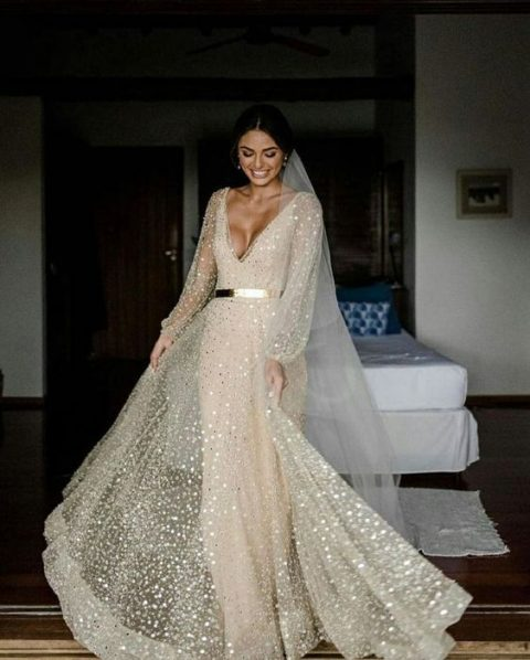 a neutral sparkling A-line wedding dress with a plunging neckline, long sleeves and a veil