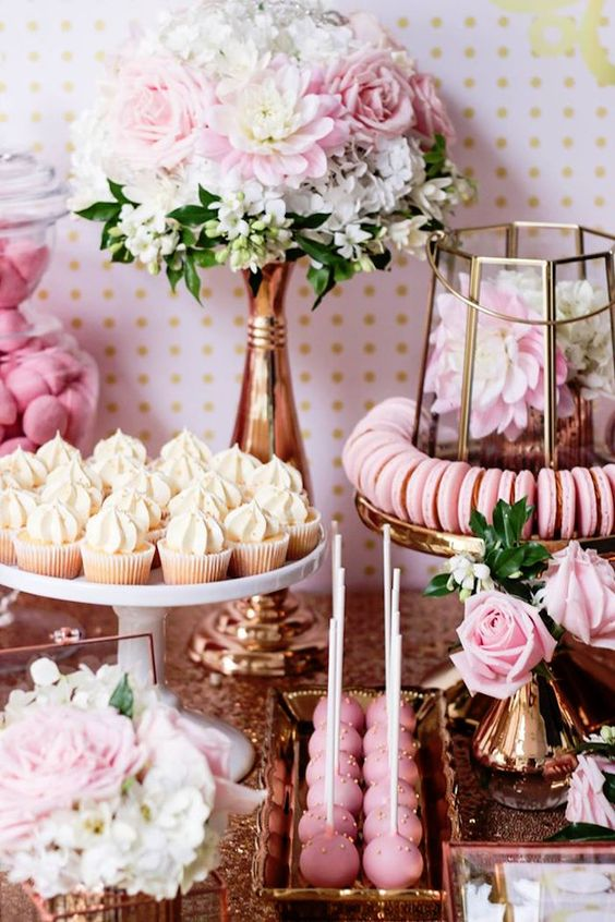 a pink dessert table with cake pops, cupcakes, cookies and lots of blooms in ivory and pink