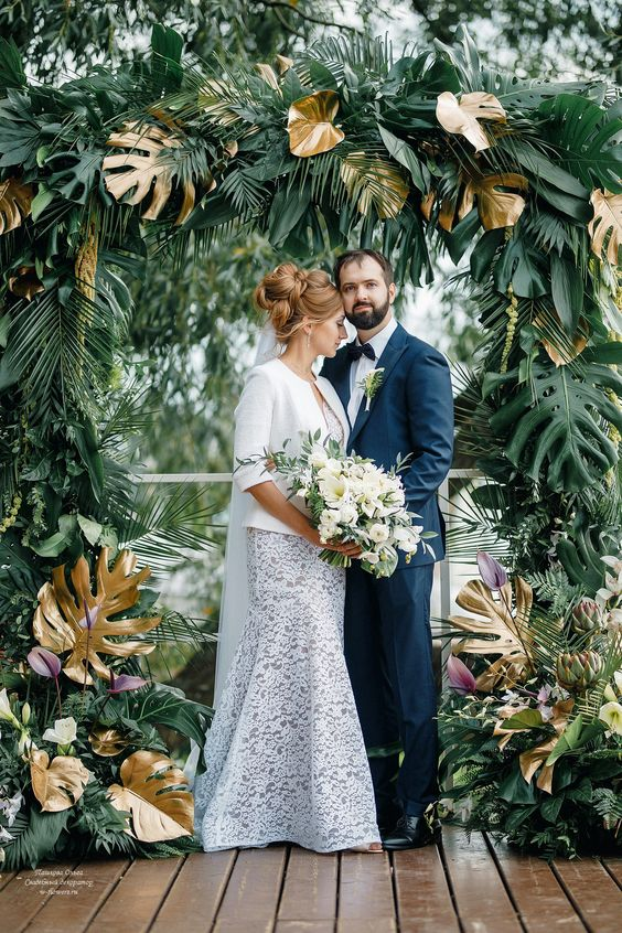 a refined wedding arch all covered with lush greenery, gilded monstera leaves and dark calla lilies