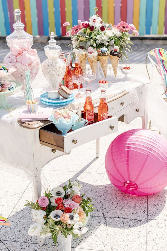 a retro-inspired dessert table with pastel sweets and plates, fresh berries, lush blooms and a paper lamp in pink