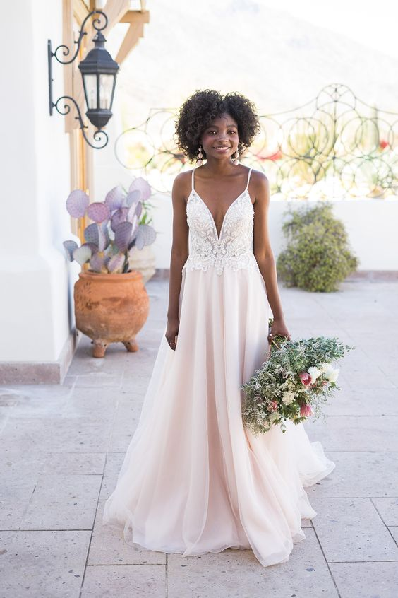 a romantic A-line wedding dress with a white lace bodice with a plunging neckline and a blush skirt