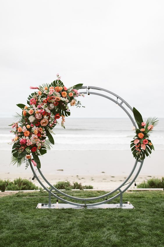 a round tropical wedding arch decorated with tropical leaves, orange, pink and white blooms