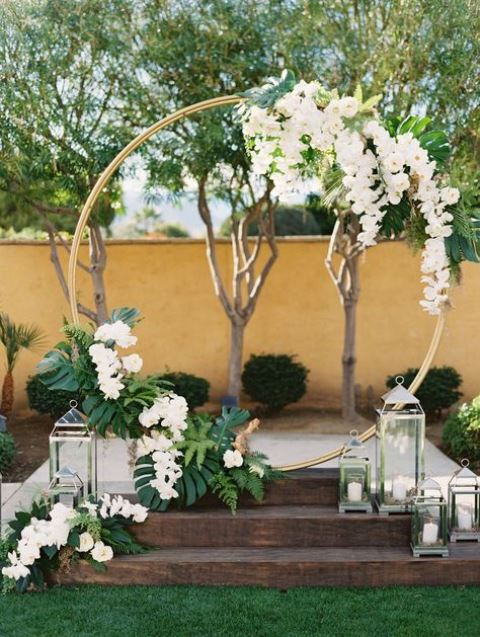 a round tropical wedding arch topped with white orchids, monstera leaves and fern ones, candle lanterns