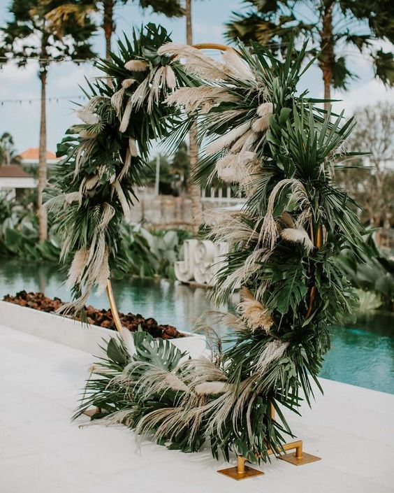 a round wedding arch done with tropical leaves and pampas grass is a cool idea for a boho wedding