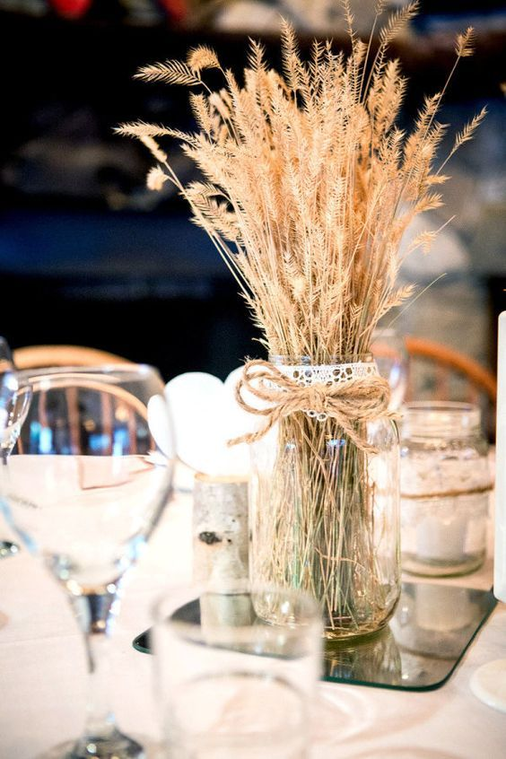 a rustic centerpiece with a mirror, a jar with wheat and twine and lace