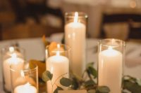a rustic chic rehearsal dinner centerpiece with candles and greenery plus gilded wooden stands and holders