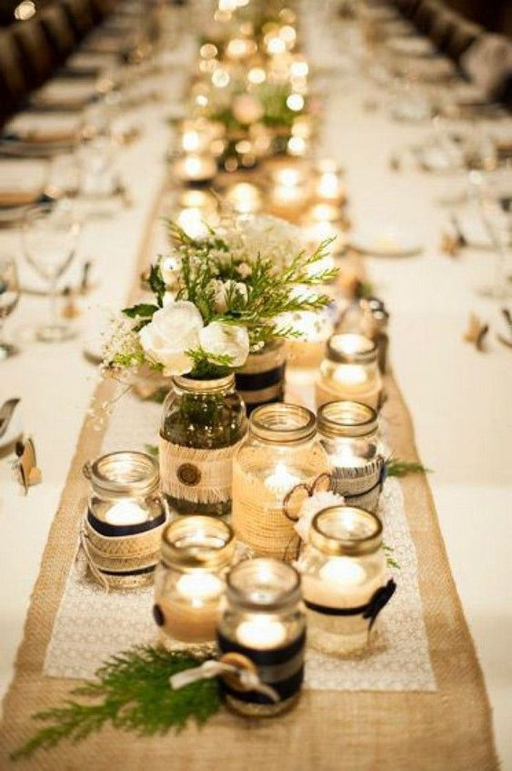 a rustic table centerpiece with jars with candles and neutral floral and greenery arrangements