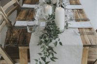 a rustic uncovered table with a white runner and greenery plus large white candles for a rustic rehearsal